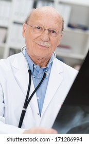 Close-up of the smiling face of a balding senior doctor wearing glasses checking an x-ray film for a prognosis or diagnosis