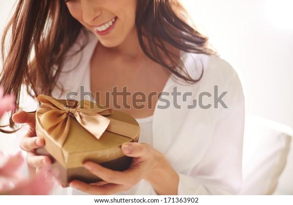 ハート形のギフトボックスを持つ笑顔の女性の接写