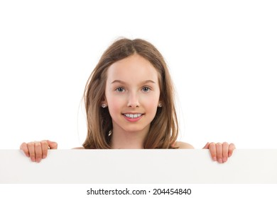 Close-up of smiling girl behind placard. Portrait of smiling young girl holding blank sheet. Head and shoulders studio shot isolated on white.