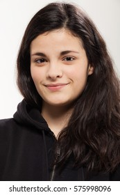 Closeup of a smiling girl with a black sweatshirt, brown hair