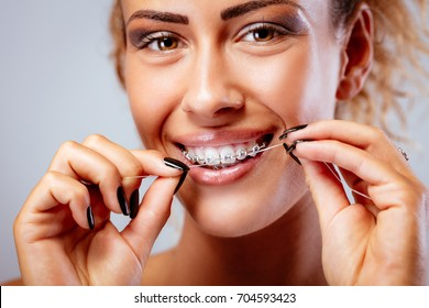 Close-up of a smiling girl with braces cleaning teeth with dental floss. Looking at camera.