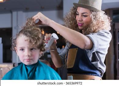 Close-up of smiling hairdresser spraying boy hair