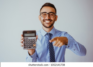 Closeup of smiling handsome young business man holding and showing calculator. Calculation concept. Isolated front view on grey background.