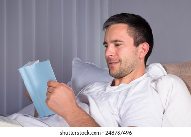 Close-up Of A Smiling Man On Bed Reading Book