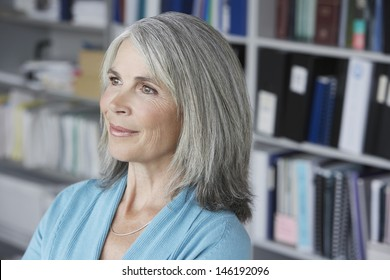 Closeup of a smiling middle aged businesswoman looking away in office