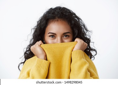 Close-up smiling pretty african american girl, curly black hair, pull sweater on face and smiling with eyes, playfully and flirty giggle, gazing camera, standing white background silly