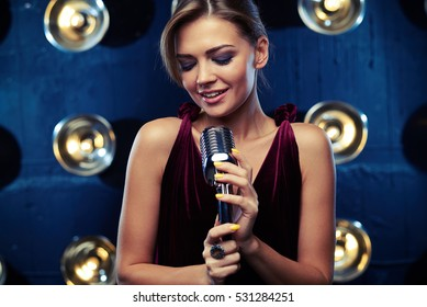 Close-up of smiling pretty woman in wonderful vinous evening dress who is holding a retro silver studio microphone over the background of blurred spotlights