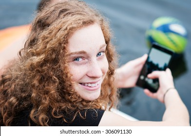 closeup of smiling teenage girl holding a cell phone