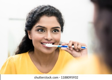 Close-up of a smiling woman brushing teeth