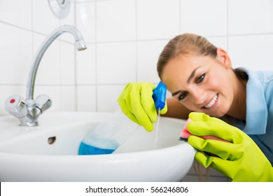 Close-up Of Smiling Woman Cleaning The Basin With Spray Bottle And Sponge In The Bathroom