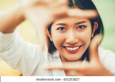 Closeup of Smiling Woman Framing Face with Fingers