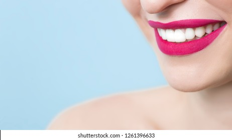 Close-up of a smiling woman with healthy white teeth, red matte lipstick, on a blue background. Dentistry concept. Copy space.