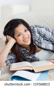 Close-up of a smiling woman holding a book in a living room
