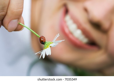close-up smiling woman holding flower camomile with ladybug outdoor