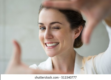 Closeup of Smiling Woman Making Frame Gesture