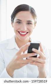 Close-up of a smiling young business woman with mobile phone