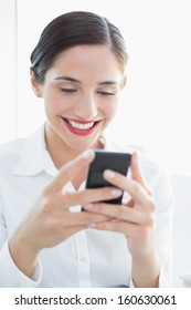 Close-up of a smiling young business woman looking at mobile phone