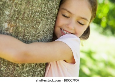 Close-up of a smiling young girl hugging tree with eyes closed at the park