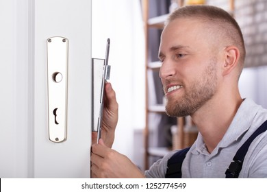 Close-up Of A Smiling Young Man Fixing Door Lock In House