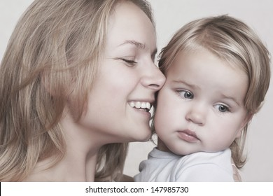 Closeup of smiling young mother caressing baby girl over colored background