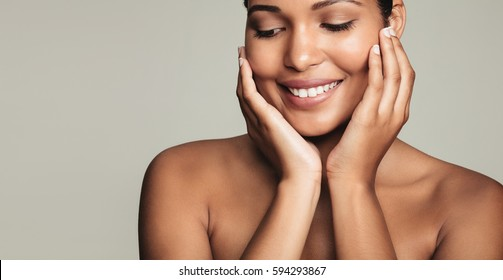 Closeup of smiling young woman with clean and healthy skin on grey background. Pretty female model touching her face.
