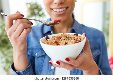 Close-up of smiling young woman eating breakfast cereals of bowl at home.