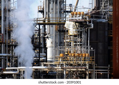 Closeup of smoke rising in front of a petrochemical plant with lots of pipes