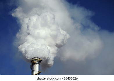 Closeup of a smoke stack, quivering with heat, spewing steam and pollutants against a clear blue sky