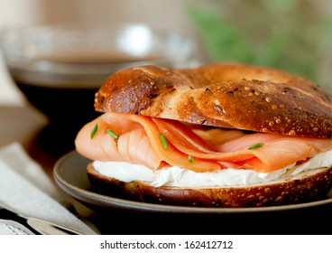 Closeup of a smoked salmon and cream cheese bagel with coffee.