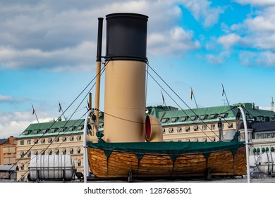 Closeup of a Smokestack and a Wooden Boat on top of a Ship in the Waters across from the Royal Palace in the Gamla Stan Neighborhood of Stockholm, Sweden