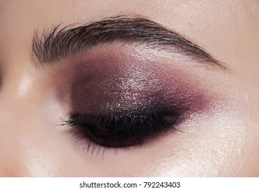 Close-up smokey eyes make-up. purple make-up with golden shimmer