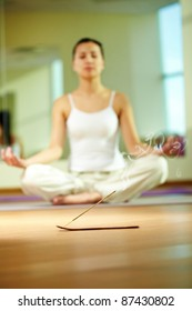 Close-up of smoking incense with serene girl doing yoga exercise on background