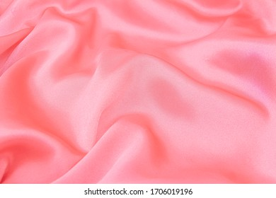 Close-up of a smooth, luxurious, pink silk or satin fabric with waves on top. Can be used for wedding, romantic background or for Valentine's day.