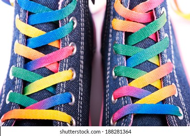 Closeup of sneakers with colored shoelaces, abstract background