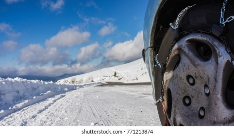 Closeup of snow chains mounted on a snowy car wheel with large copy space on its left.