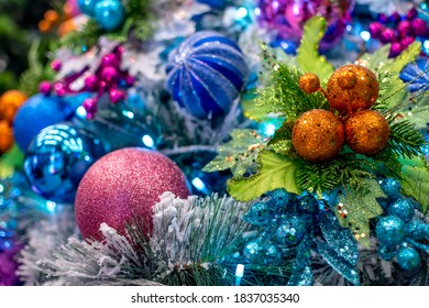 Closeup of a Snow Vinyl Chirstmas Tree decorated with colorful balls and ornaments, and blue LED lights. Displayed at a local shop or department store for sale.