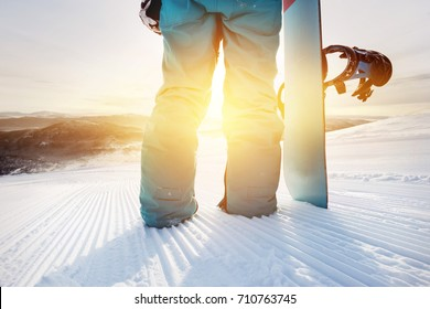 Closeup snowboarding concept. Girl snowboarder holding snowboard on ski slope at sunrise or sunset time