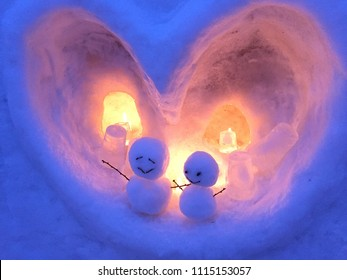Closeup of snowman lovers with happy and smile facial expression inside an ice cave with candle light at Otaru Snow Festival Hokkaido Japan