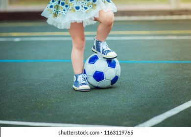 close-up of a soccer ball and legs of a girl on a soccer field