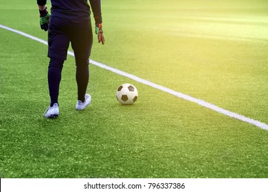 Closeup of a soccer ball and soccer player at the stadium. A beautiful football field with markings.