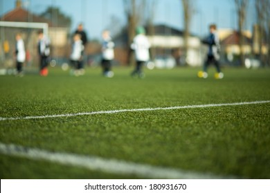 Close-up of soccer field with blurred children playing a soccer match in the background.