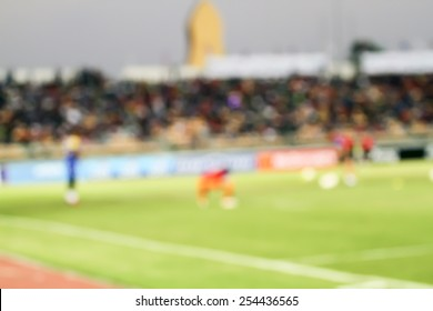 Close-up of soccer field with blurred playing a soccer match in the background.