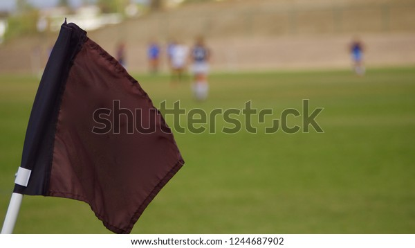Close-up of a soccer flag girl players in background with shallow depth of field.