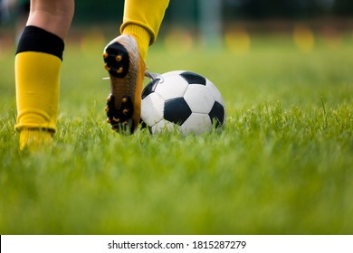 Closeup of soccer player running and kicking soccer ball on grass lawn. Legs of footballer playing competition match. Sports horiznotal background. Athlete in soccer cleats and soccer socks
