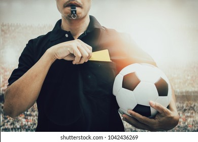 Closeup of  soccer referee hand holding yellow card punishment in the stadium during match