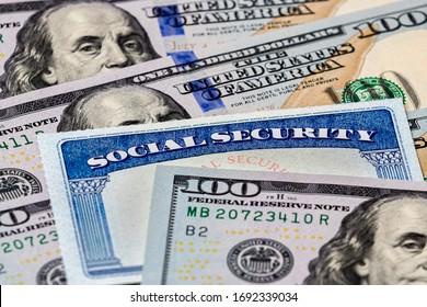 Closeup of Social Security benefits identification card with 100 dollar bills