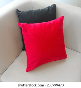 Close-up of sofa corner with red and gray cushions.