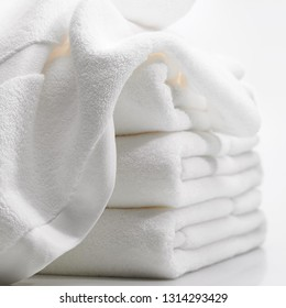 CLOSE-UP OF SOFT COTTON WHITE TOWELS OVER THE WHITE BACKGROUND. WHITE TOWEL ISOLATED. SPA AND HOTEL TOWELS