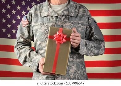 Closeup of a soldier holding a Christmas present, standing in front of American Flag. The gift is wrapped in gold paper with red ribbon and bow.