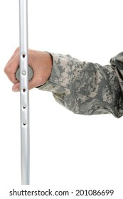 Closeup of a soldier holding onto the hand grip of a crutch. Only his hand and arm are visible. The man is wearing camouflage fatigues isolated over white.